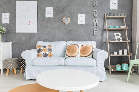 Woonkamer met comfortabele sofa, ronde tafel en eenvoudige regale