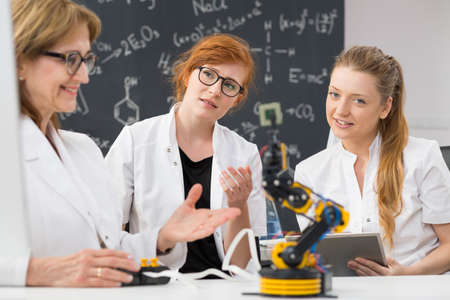 talking robot: Shot of technical university students working with their teacher on creating a robot Stock Photo