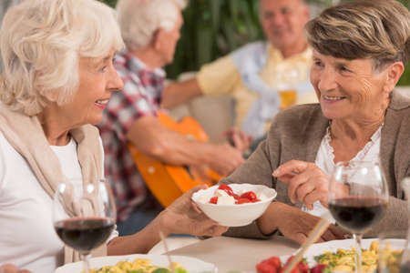 eating dinner: Two senior women talking and drinking wine during dinner Stock Photo