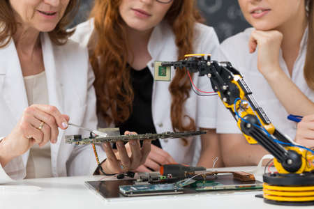 mainboard: Cropped picture of three women working on a mainboard