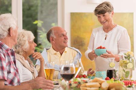 Amici felici maggiori che godono un pasto serale
