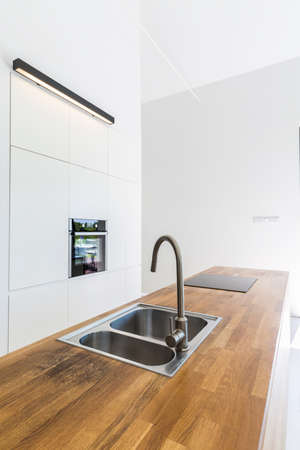 steely: Modern minimalist kitchen with white walls, built-in cabinets and wooden table top