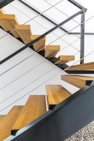 steely: Minimalist staircase with wooden steps and white wall Stock Photo