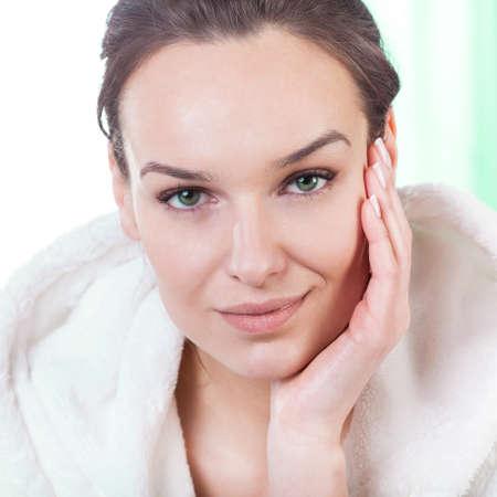 Portrait de la belle jeune femme de toucher son visage