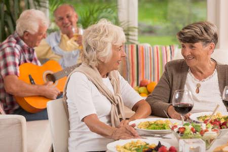 matrimonio feliz: Dos mujeres mayores que hablan y que beben el vino, en el fondo anciano que toca una guitarra