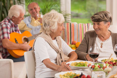 Two senior women talking and drinking wine, in the background elderly man playing a guitar