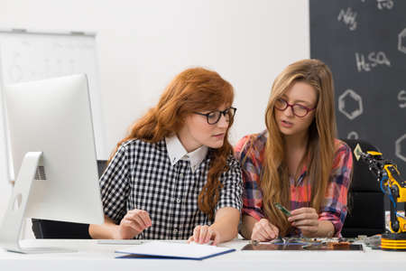 talking robot: Shot of two focused geek students in a classroom, discussing the results Stock Photo