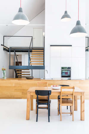 APARTMENT LIVING: Minimal modern house with white walls, wooden furnitures and stairs leading up to attic Stock Photo
