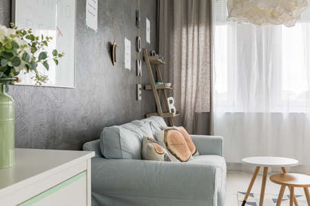blue wall: Living room with sofa, small round table and window curtains Stock Photo