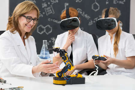 Shot of a professor and two science students wearing VR goggles