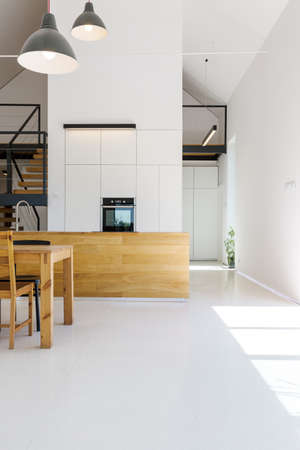 Modern minimalist kitchen with wooden furnitures, white walls and high ceiling
