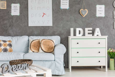 Gezellig interieur met eenvoudige blauwe bank, dressoir en tafel Stockfoto