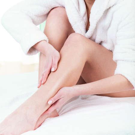 Žena si třepe krém na nohou po depilaci Reklamní fotografie