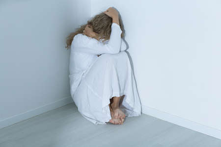 suicidal: Young mental hospital patient with an anxiety disorder sitting on a floor covering her face