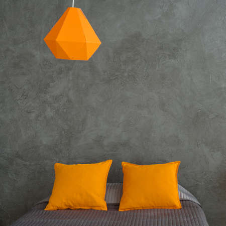 yellow walls: Bedroom with grey walls and bed and colorful additions. Orange pillows, lamp and yellow chair in grey dark room