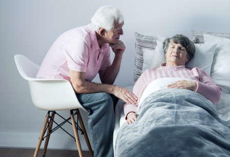 persona de la tercera edad: El hombre mayor apoyo a su mujer enferma acostada en la cama Foto de archivo