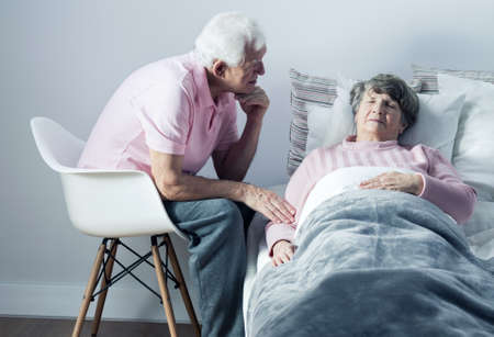 home care: Elderly man supporting his ill wife lying in bed