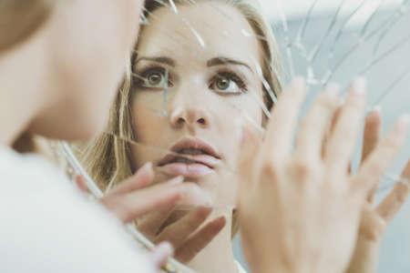 분열 된 거울에 반영 된 정신 분열증 여자의 얼굴