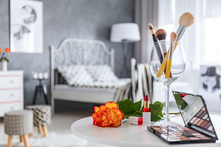 Make-uptoebehoren die op witte rondetafel in grijze slaapkamer liggen
