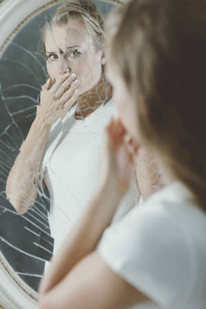 Broken mirror reflection of depressed woman covering her mouth Stock Photo