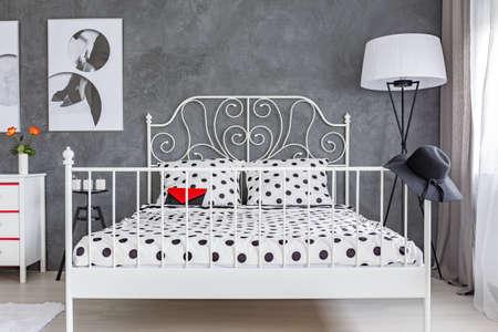 mujer sola: habitación gris con gran cama con cabecero de metal decorativos