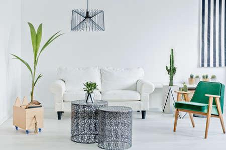Woonkamer met groene fauteuil, opengewerkte tafel en bank Stockfoto
