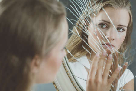 Beautiful woman with mental disorder touching broken mirror
