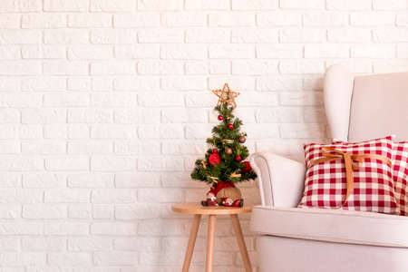 nightstand: Little christmas tree on a nightstand near the white sofa