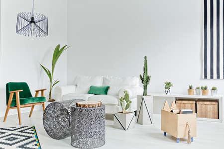 Witte woonkamer met bank, opengewerkte tafel, tapijt en fauteuil