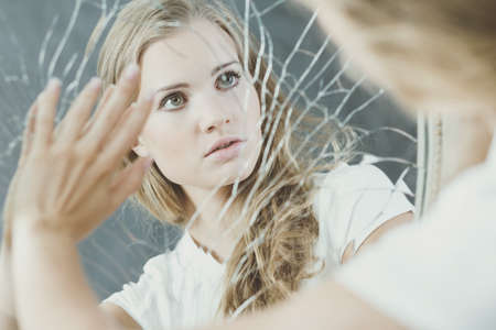desorden: adolescente con trastorno de la personalidad tocar espejo roto Foto de archivo