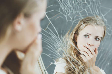 mirror: Girl with mental problem looking at herself in a mirror Stock Photo