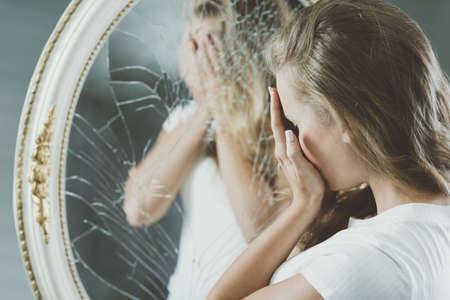 Frau mit psychischen Problemen, die ihr Gesicht spiegelt sich im Spiegel
