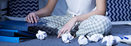 sleeplessness: Panoramic photo of woman sitting in pajamas in bed with smashed papers in front of her