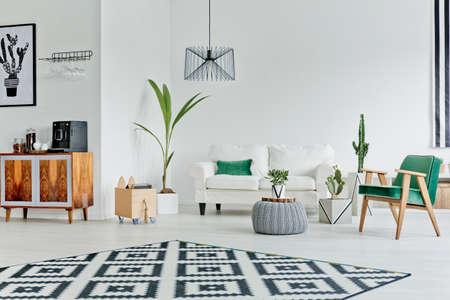 Ruime witte kamer met patroon tapijt, bank en fauteuil Stockfoto - 66121063