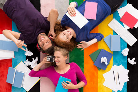 Shot of three friends relaxing on a colorful carpet surrounded by notebooks