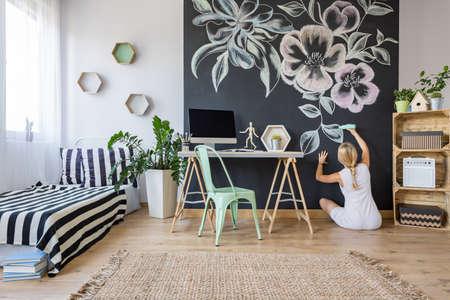 多機能ホーム インテリアの黒板壁の花に引っ張っている女
