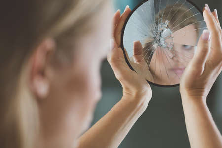 reflection in mirror: Woman with mental disorder holding small broken mirror Stock Photo