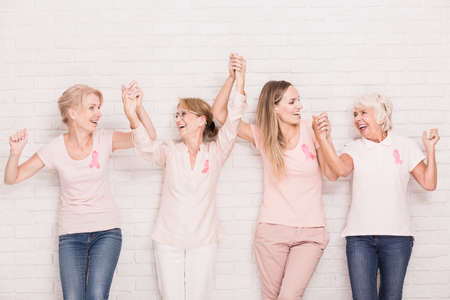 Positive cancer survivors wearing pink, holding each other hands Imagens