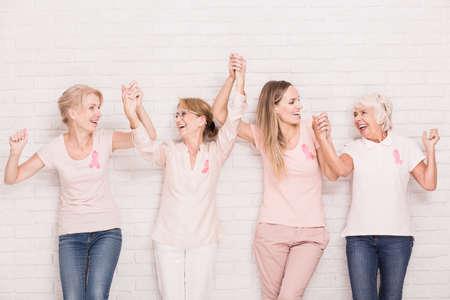 sopravvissuti al cancro positivi indossando rosa, che si tengono le mani Archivio Fotografico