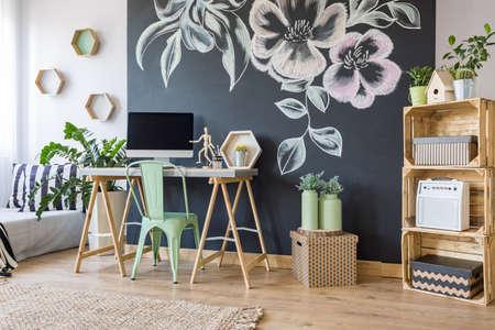 Home werkruimte met krijtbord, diy, regale, bureau, stoel en computer Stockfoto