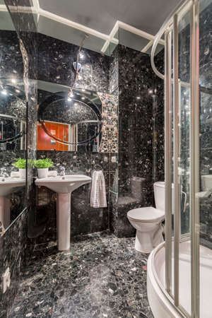 marble stone: Ethnic bathroom interior in grey marble colous, with sink, mirror above, backlight, toilet and the shower