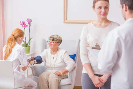 ilness: Nurse checking blood pressure for elderly lady while her daughter talks with doctor