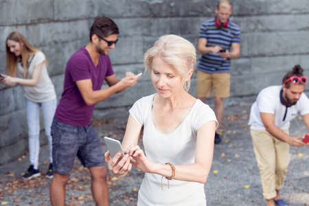 cell phone addiction: Woman with mobile phone outdoors standing among people using cell phones