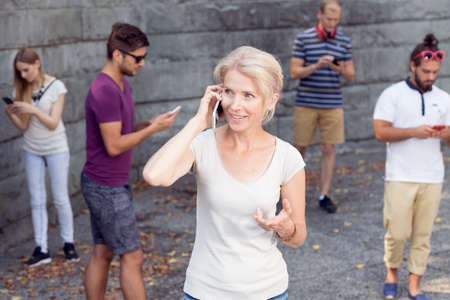 cell phone addiction: Woman talking on mobile phone, people with cell phones in background