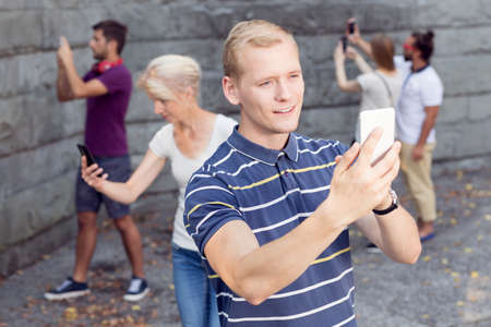 cell phone addiction: Young man taking selfie with his phone