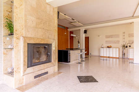 open plan: Spacious and bright area of living room with the marble fireplace, floor and view of open plan kitchen area