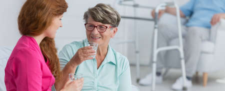 home keeping: Woman taking the medicine in front of nurse