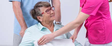 Careful nurse covering senior woman by blanket