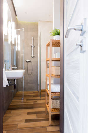 bathroom tiles: Photo of a narrow bathroom with floor tiles resembling wood and glass shower enclosure