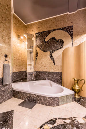 interior wall: Ethnic elegant bathroom interior with gold and grey colous, with bathtub, shower, mosaic on the wall, towel and gold jug Stock Photo